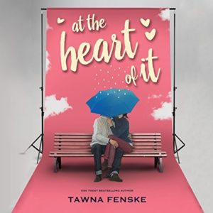 A couple sits on a bench in an embrace, their faces covered by a blue umbrella. The backdrop is pink with white clouds and the book's title - it's set up to look like a photo shoot