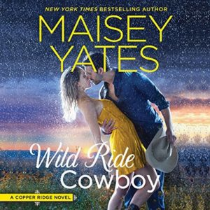Fair-haired white woman in a yellow sundress kissing a dark-haired cowboy in a blue shirt in the rain in a field