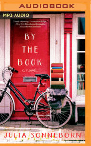 A bicycle with a load of hardback books on a carrier behind the seat rests against a red door. It has nothing to do with the book!